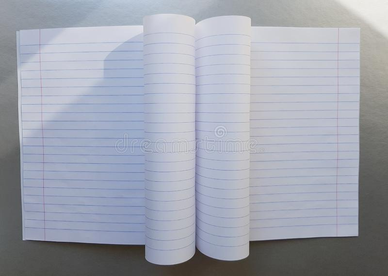 Open school notebook with pen on a gray desk with sun rays from the window. A blank, white sheet of notebook for writing. stock image