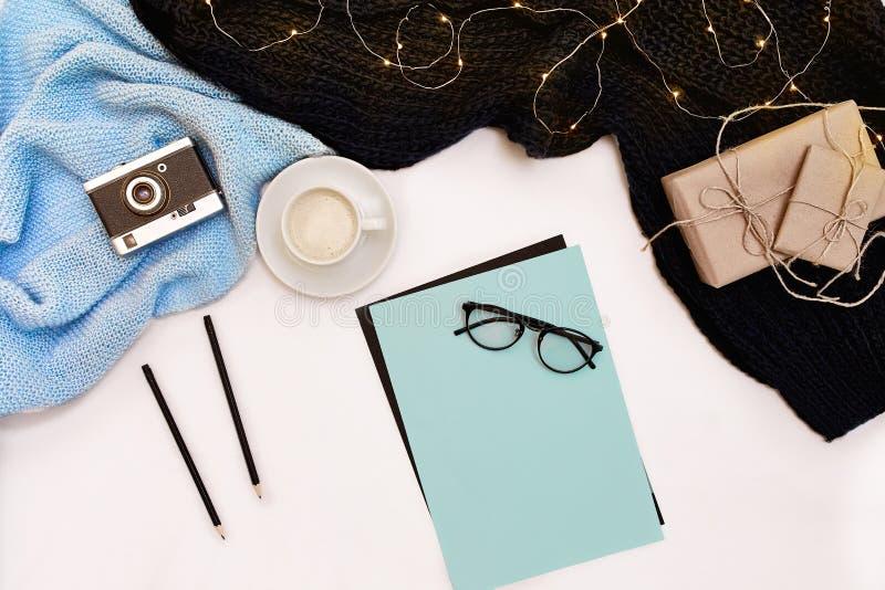 Open schoon notitieboekje voor uw tekst, pen, giftvakjes, sjaal en Kerstmislichten op witte achtergrond, hoogste mening royalty-vrije stock foto's