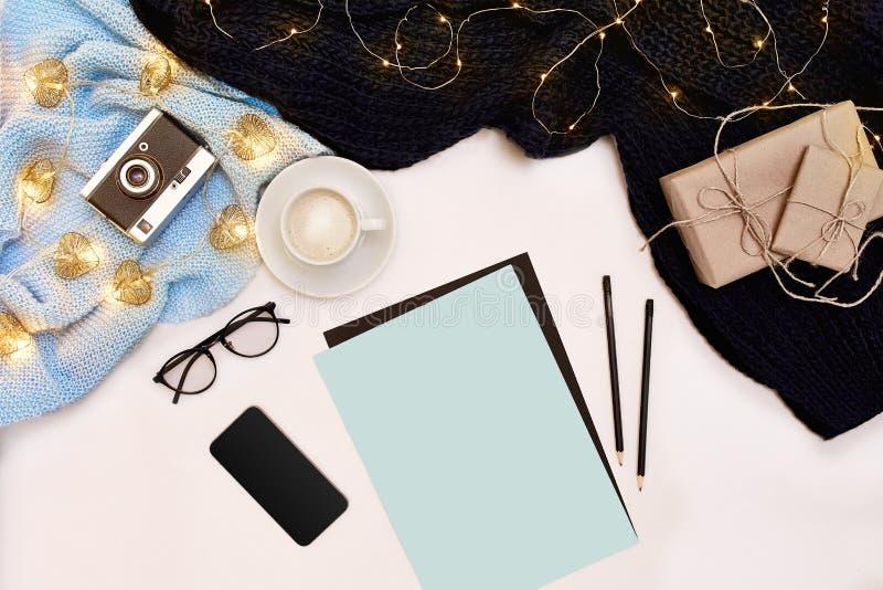 Open schoon notitieboekje voor uw tekst, pen, giftvakjes, sjaal en Kerstmislichten op witte achtergrond, hoogste mening stock afbeeldingen
