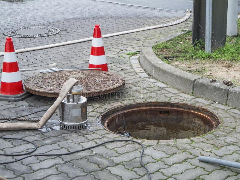 Open sewer with pump and manhole cover royalty free stock photography