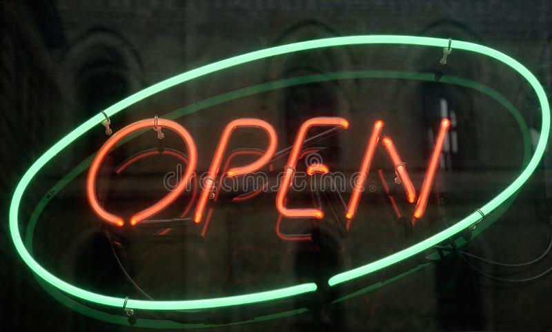 Open, shining neon sign stock image