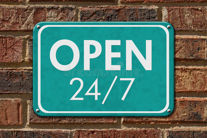 Open 24 / 7 Sign. A teal hanging sign with text Open 24 / 7 on a brick wall stock image