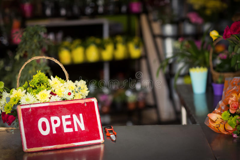 Open signboard on table. At flower shop stock image