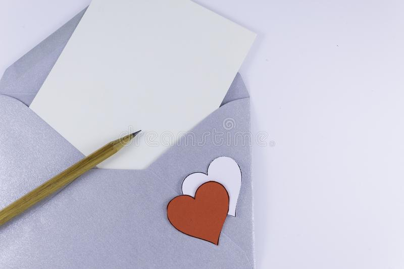 Open silver envelope with blank white letter with a wooden pencil next to and two white and red hearts near on a white background. The concept of minimalism royalty free stock photo