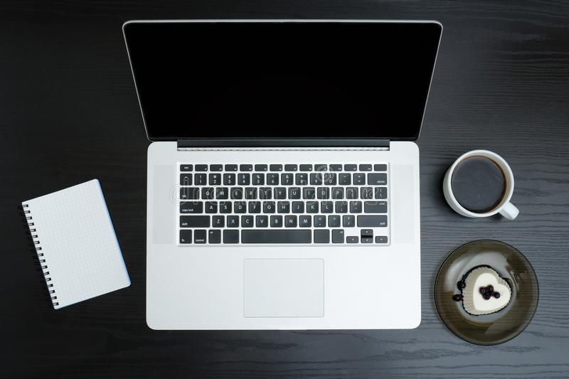 Open silver laptop, mug of coffee, note pad and dessert on a black background stock photography