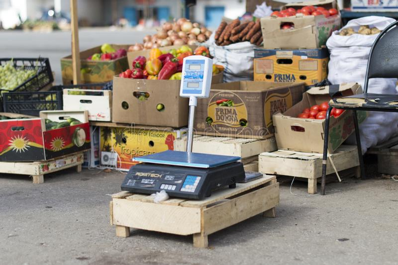 Electronic scales in the agricultural market in the background of boxes and nets represent vegetables and fruits. stock photos
