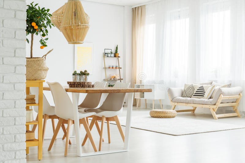 Open space with dinner table. White chairs and comfortable, grey sofa royalty free stock photography