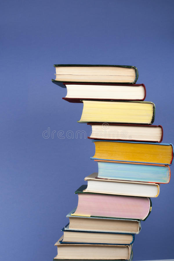Open stacking book, hardback colorful books on wooden table and blue background. Back to school. Copy space for text stock images
