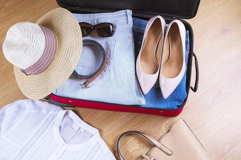 Open suitcase with casual woman clothes hat, sunglasses, white shirt, shoes, bag on wooden floor top view close up. Packing travel royalty free stock image