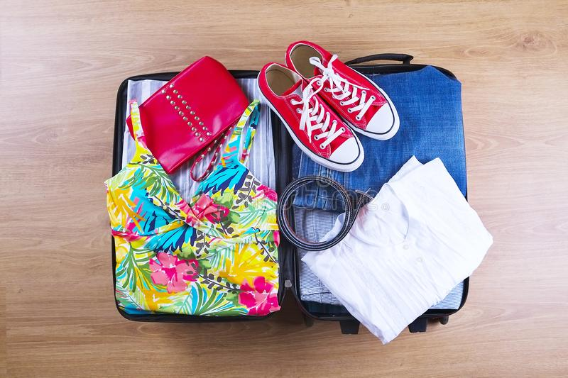 Open packed suitcase with female summer clothes and accessories, bathing suit, sneakers, white shirt on wooden floor top view royalty free stock photos
