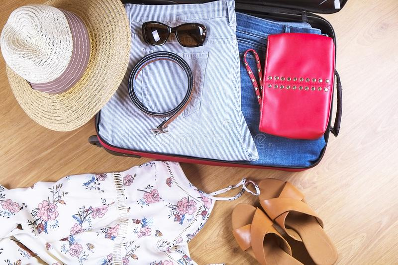 Open suitcase with casual female clothes hat, sunglasses, dress, shoes, on wooden floor top view close up. Packing travel bag for stock image