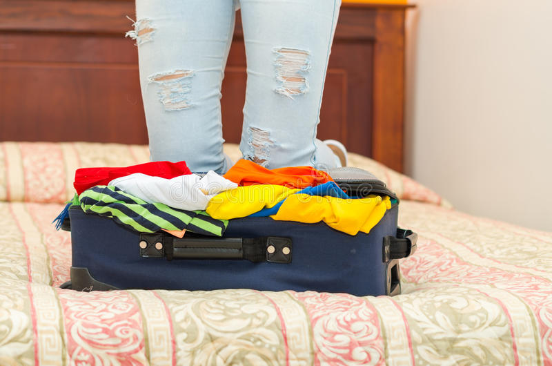 Open suitcase with clothes inside lying on bed, womans legs in background, hostel guest concept stock images