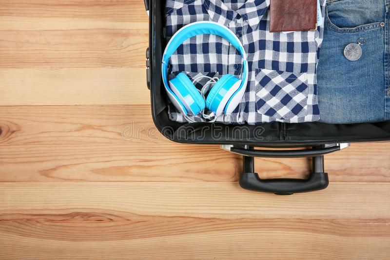 Open suitcase with clothes and tourist's stuff on wooden background royalty free stock images