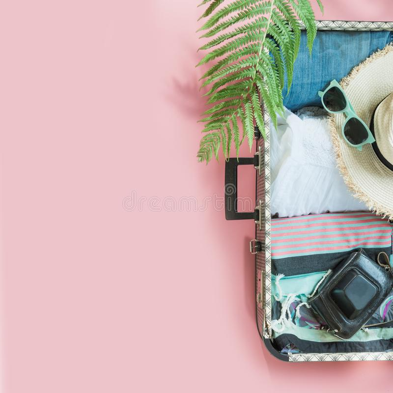 Open suitcase with female clothes for trip on pastel pink. Top view with copy space. Summer concept travel royalty free stock images