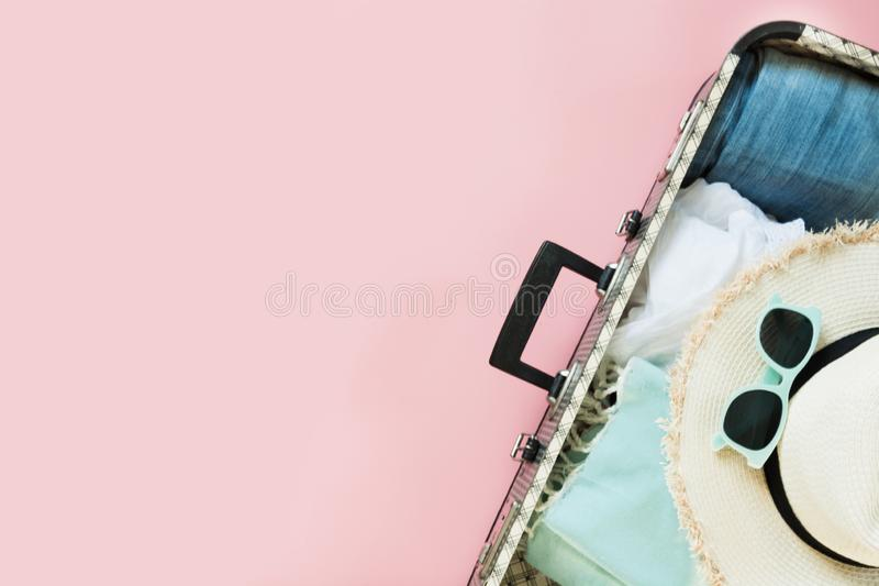 Open suitcase with female clothes for trip on pastel pink. Top view with copy space. Summer concept travel. Open suitcase with female clothes for trip on pastel royalty free stock photography