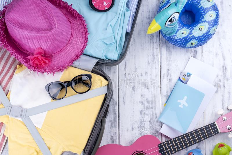 An open suitcase with things for the holidays and the sea. Bright Clothes, guitar and accessories. Passport and documents for the stock images