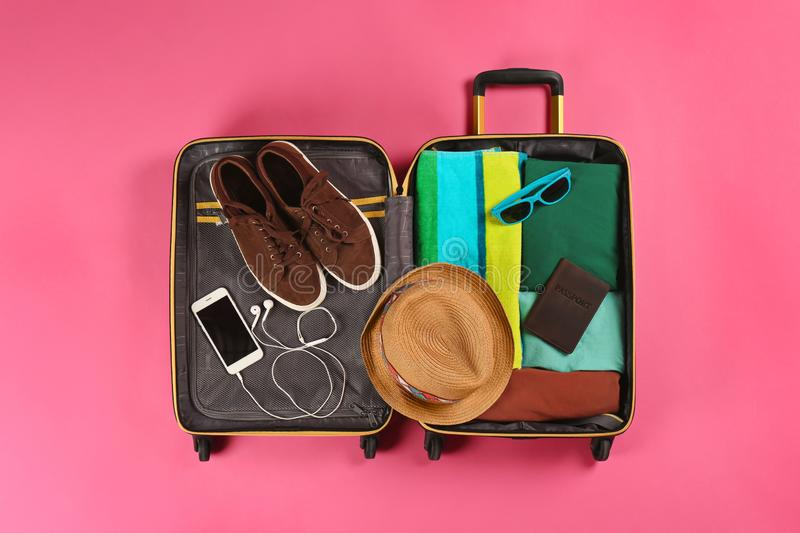 Open suitcase with traveler`s belongings on color background. Top view stock image