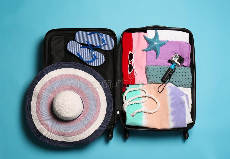 Open suitcase with traveler`s belongings on color background. Top view stock images