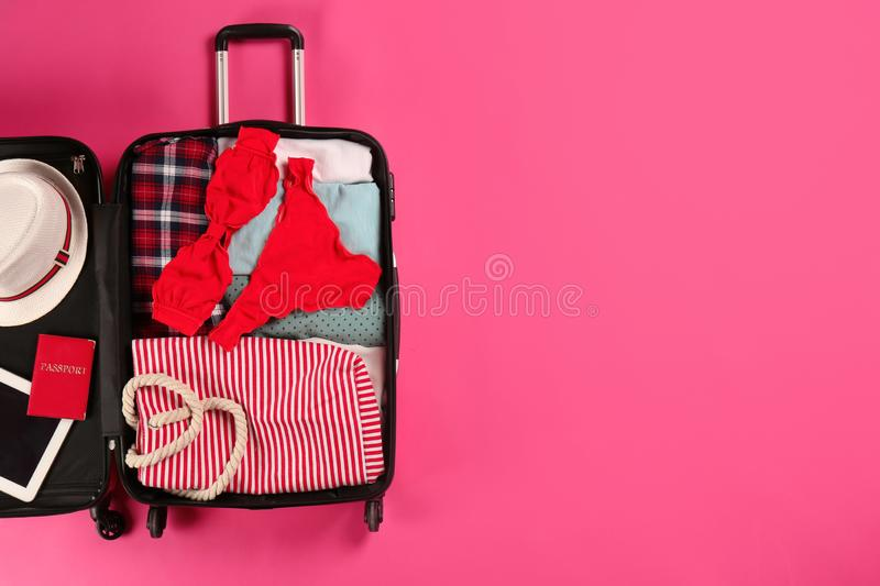 Open suitcase with traveler`s belongings on color background, top view. Space for text royalty free stock images