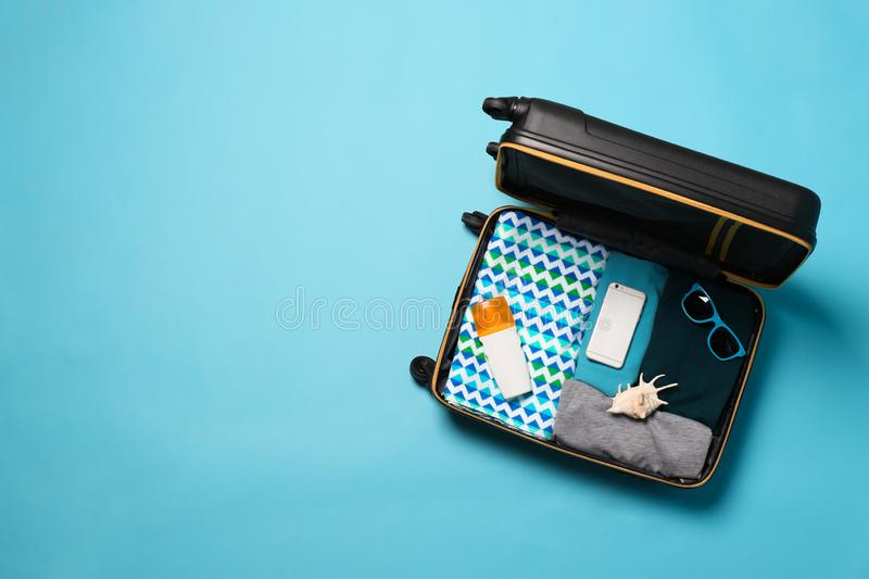 Open suitcase with traveler`s belongings on color background, top view. Space for text royalty free stock photography