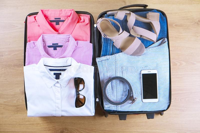 Open suitcase with trendy female clothes and accessories on wooden floor top view, copy space, vintage toned image. Packing luggag royalty free stock photos