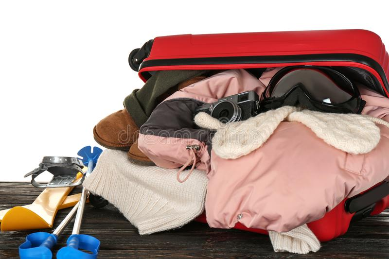 Open suitcase with warm clothes and ski outfit stock image