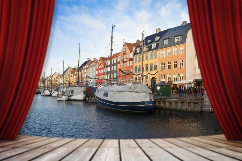 Open theater red curtains against Nyhavn city during the Christmas holidays - Europe - Denmark - Copenhagen - concept image.  royalty free stock photo