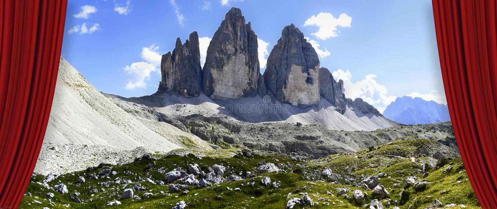 Open theater red curtains against the Tre Cime di Lavaredo panoramic view in summer - Dolomitics landscapes Italy. View of San Nicolò refuge in Contrin valley stock photo