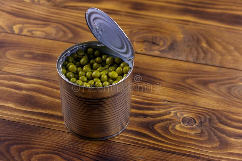 Open tin can of green peas on wooden table. Open tin can of green peas on a wooden table royalty free stock image
