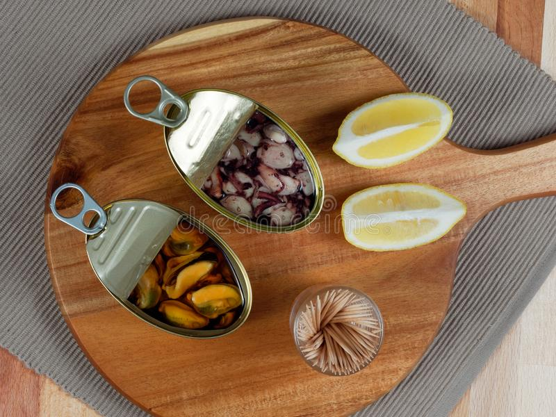 Open tin cans of mussels and octopus on a rustic wooden board. Cans of preserves with mussels and octopus on a rustic wooden board, with lemon slices and royalty free stock photography