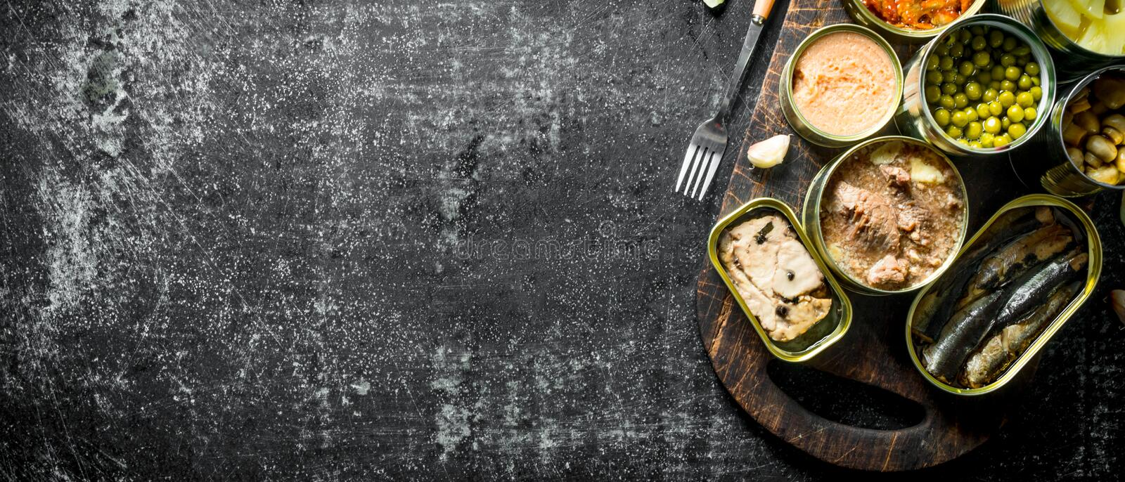 Open tin cans with various canned food on wooden cutting Board. On dark rustic background royalty free stock image