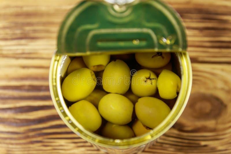 Open tinblik van groene olijven op houten lijst Hoogste mening royalty-vrije stock afbeeldingen