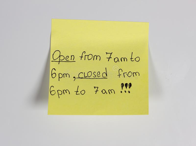 Open from 7 am to 6 pm, closed from 6 pm to 7 am,yellow sticker on the door fridge magnet stock images