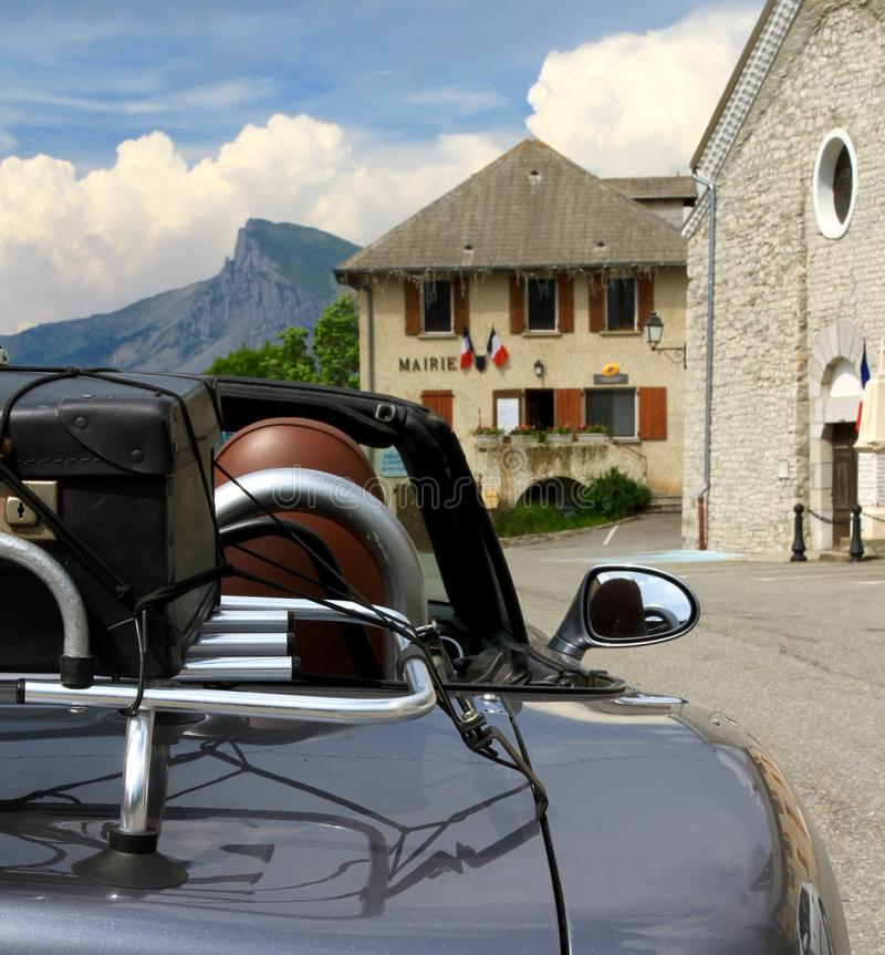 Open top Mazda MX5 with suitcase on a rack against a Marie in the French Alps. Open top Mazda MX5 with suitcase on a rack against a Marie & x28;town hall& x29 royalty free stock photography