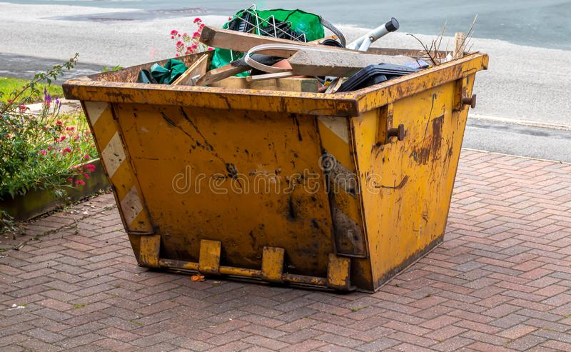 An open topped skip awaiting collection. A yellow skip full of rubbish ready to be collection stock image