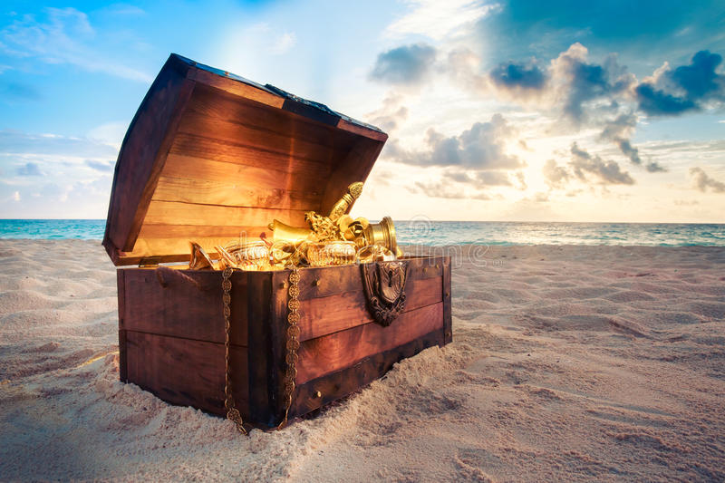 Open treasure chest on the beach. Open treasure chest with shinny gold stock photos