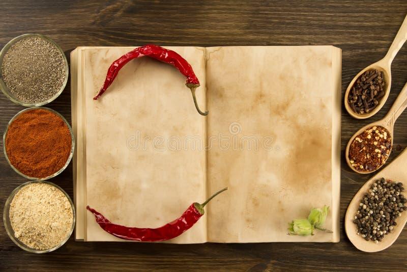 Open uitstekend boek met kruiden op houten achtergrond Gezond vegetarisch voedsel Recept, menu, spot omhoog, het koken stock foto's