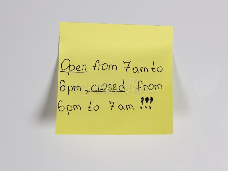 Open van 7 am voor 6 p.m., van 6 p.m. aan 7 am, gele sticker op de magneet die van de deurkoelkast wordt gesloten stock afbeeldingen