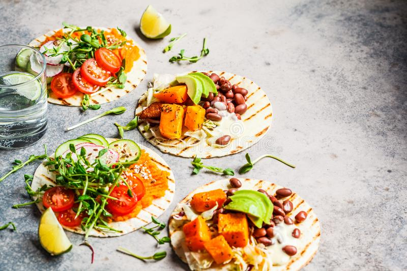 Open vegan tortilla wraps with sweet potato, beans, avocado, tomatoes, pumpkin and  sprouts on gray background, flat lay, copy. Open vegan tortilla wraps with royalty free stock images