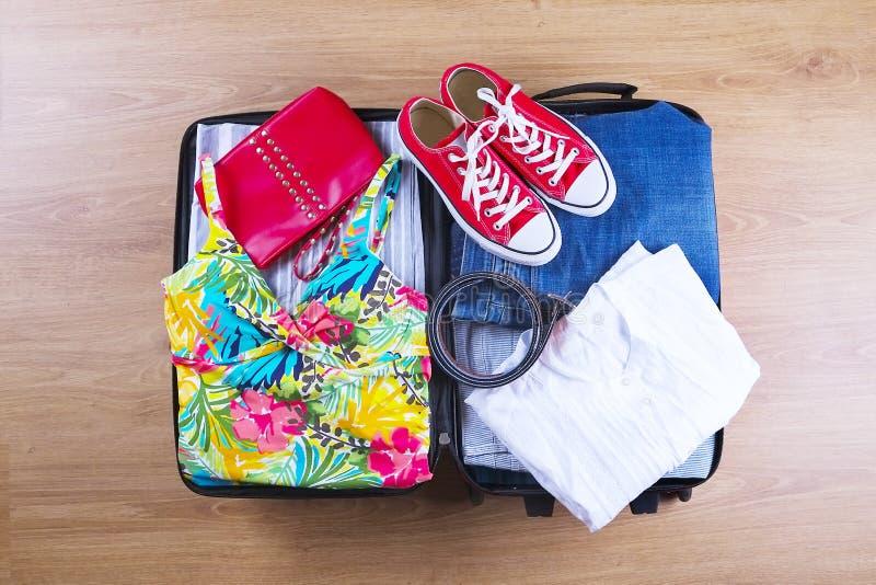 Open verpackte Koffer mit weiblicher Sommerkleidung und Zubehör, Badeanzug, Turnschuhe, weißes Hemd auf Draufsicht des Bretterbod lizenzfreie stockfotos