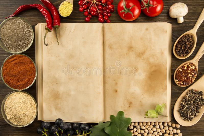 Open vintage book with spices on wooden background. Healthy vegetarian food. Recipe, menu, mock up, cooking. royalty free stock image