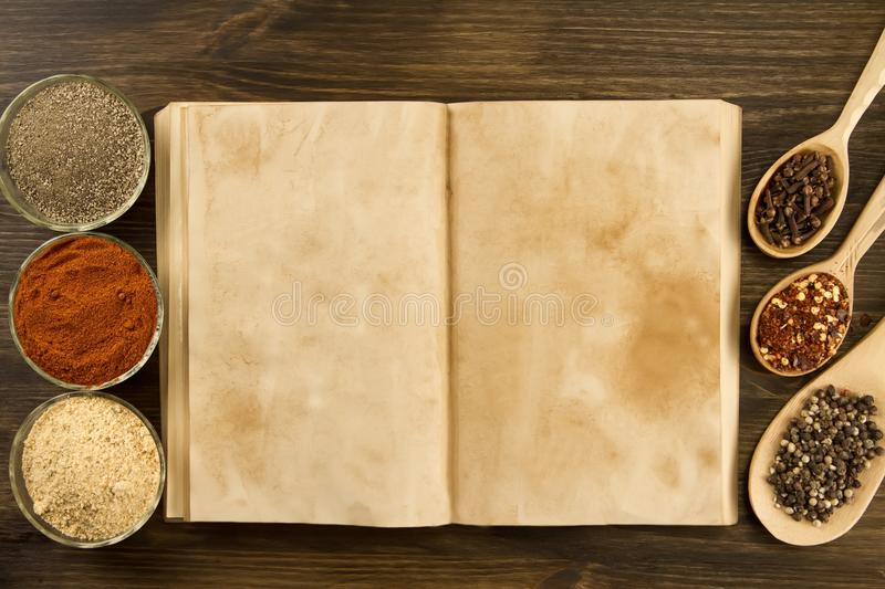 Open vintage book with spices on wooden background. Healthy vegetarian food. Recipe, menu, mock up, cooking. Open old vintage book with spices on wooden royalty free stock images