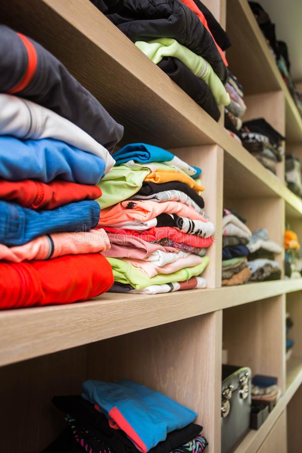 Open wardrobe with lots of folded clothes stock images
