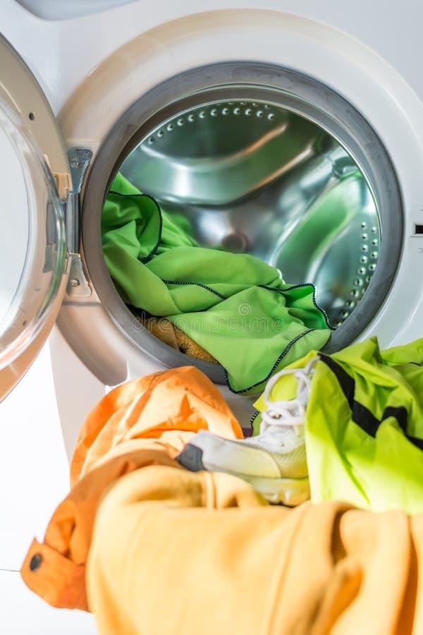 Open wasmachine met kleurrijke lading - verticaal stock foto's