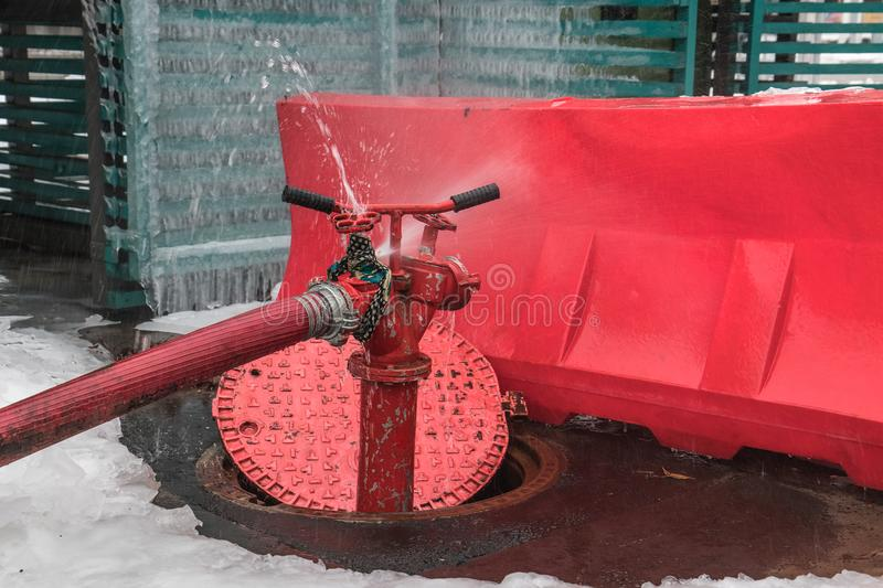 Open water intake well and fire hydrant. Jet of water escapes from the faulty tap stock image