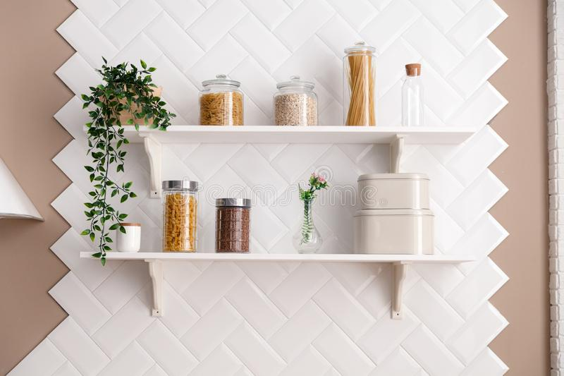 Open white kitchen shelves, cereals and pasta in glass jars, spaghetti, flower in pot, glass bottle, vase on the background of a royalty free stock photography