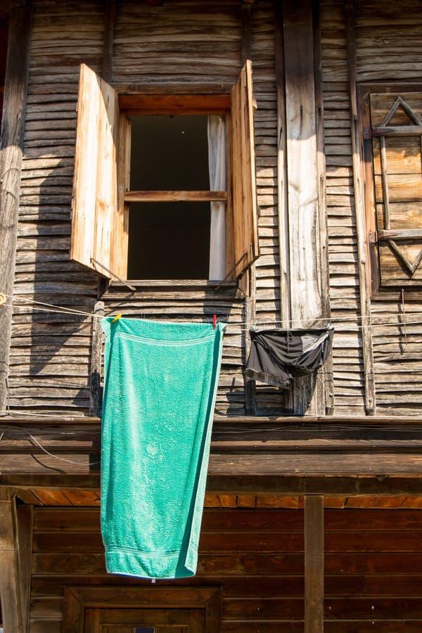 Open wijd houten venster van een oud huis met een hangende handdoek en een paar broek royalty-vrije stock afbeeldingen