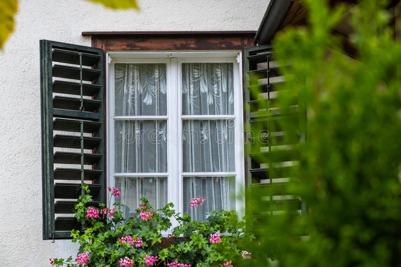 Open Window on the Facade of a white local traditional old House decorated with flower in a European style at countryside village. View of an open Window on the royalty free stock image