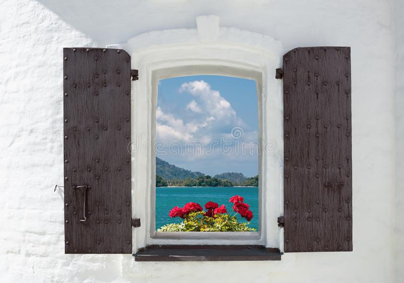 window in an old house decorated with flowers and sea view royalty free stock image