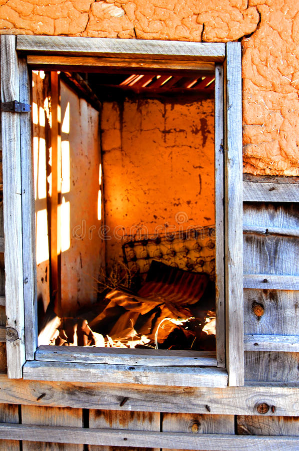 Open Window View of Adobe. Abandoned adobe home sits open to the elements. Interior can be seen through window and has remains of bed springs, roof tin, and stock images